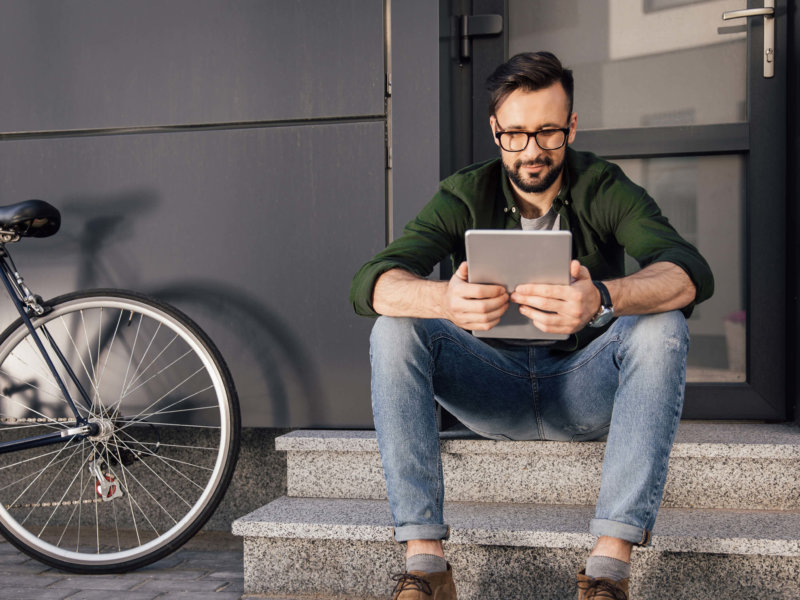 Bearded Young Man Using Tablet Sitting Stairs