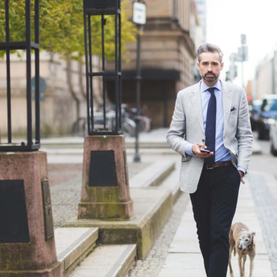 Male Suits Walking Sidewalk Near His Dog