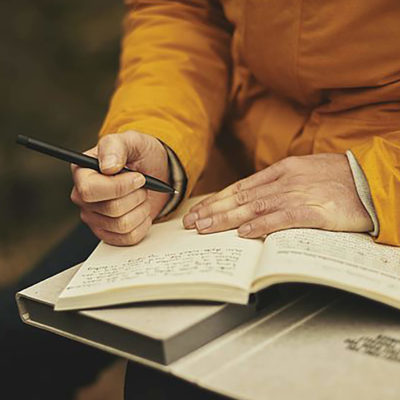 adult journal writing wearing yellow jacket